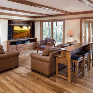 Esempio di un grande soggiorno stile americano aperto con pareti beige, pavimento in legno massello medio, camino classico, cornice del camino in mattoni, TV nascosta e pavimento marrone