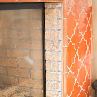 フェニックスの大きいサンタフェスタイルのおしゃれなオープンリビング (オレンジの壁、テラコッタタイルの床、コーナー設置型暖炉、タイルの暖炉まわり、埋込式メディアウォール、オレンジの床) の写真
