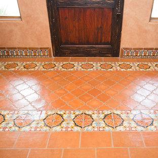 Ispirazione per un grande soggiorno stile americano aperto con pareti arancioni, pavimento in terracotta, camino ad angolo, cornice del camino piastrellata, parete attrezzata e pavimento arancione