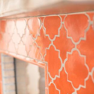 Immagine di un grande soggiorno stile americano aperto con pareti arancioni, pavimento in terracotta, camino ad angolo, cornice del camino piastrellata, parete attrezzata e pavimento arancione