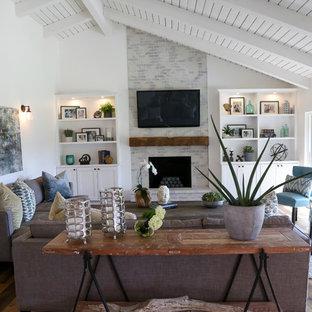 Modelo de sala de estar abierta, de estilo de casa de campo, grande, con chimenea tradicional, marco de chimenea de ladrillo, televisor colgado en la pared y suelo de madera en tonos medios