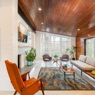 Foto di un soggiorno minimalista di medie dimensioni e aperto con pareti bianche, cornice del camino in mattoni, TV a parete e pavimento grigio