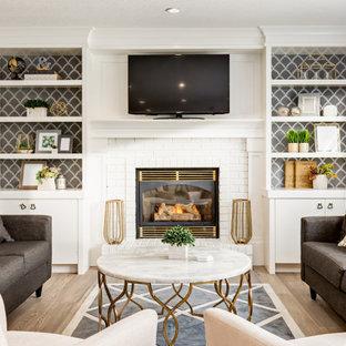 カルガリーのコンテンポラリースタイルのおしゃれなオープンリビング (グレーの壁、淡色無垢フローリング、薪ストーブ、レンガの暖炉まわり、埋込式メディアウォール、ベージュの床) の写真