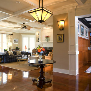 Inspiration for a craftsman open concept dark wood floor family room remodel in Charleston with beige walls