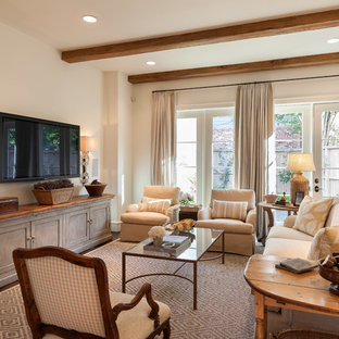 Inspiration for a mid-sized traditional enclosed family room in Houston with beige walls, a wall-mounted tv, dark hardwood floors and no fireplace.