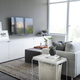 Imagen de sala de estar abierta, actual, pequeña, sin chimenea, con paredes grises, suelo de madera en tonos medios, televisor colgado en la pared y suelo gris