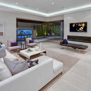 Example of a large trendy open concept porcelain floor family room design in Los Angeles with a ribbon fireplace, white walls, a plaster fireplace and a wall-mounted tv