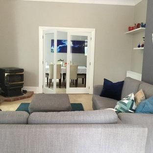 ダニーデンの大きいコンテンポラリースタイルのおしゃれなファミリールーム (グレーの壁、カーペット敷き、コーナー設置型暖炉、レンガの暖炉まわり、据え置き型テレビ、ベージュの床) の写真