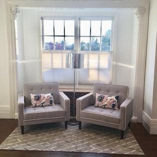 Imagen de sala de estar con biblioteca cerrada, tradicional, pequeña, con paredes blancas, suelo de madera oscura, chimenea de esquina, marco de chimenea de madera y suelo marrón
