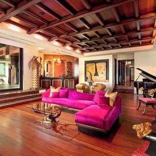 Ejemplo de sala de estar con barra de bar cerrada, de estilo zen, extra grande, con paredes beige, suelo de madera oscura y televisor retractable