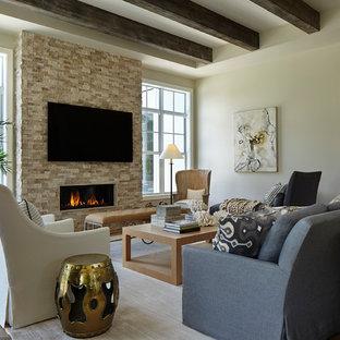 Ejemplo de sala de estar clásica renovada con paredes blancas, suelo de madera clara, chimenea lineal, marco de chimenea de piedra y televisor colgado en la pared