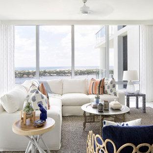 マイアミのビーチスタイルのおしゃれなファミリールーム (マルチカラーの壁、据え置き型テレビ、白い床) の写真
