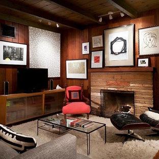 Mittelgroßes, Abgetrenntes Mid-Century Wohnzimmer mit brauner Wandfarbe, Terrakottaboden, Kamin, Kaminumrandung aus Stein, freistehendem TV und braunem Boden in Santa Barbara