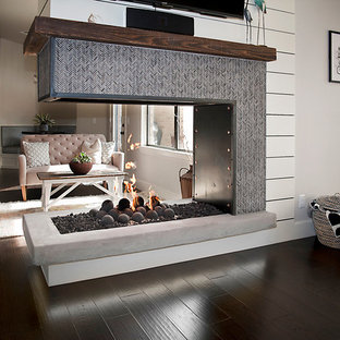 Idee per un grande soggiorno minimalista aperto con parquet scuro, cornice del camino piastrellata, pareti bianche, camino bifacciale e TV a parete