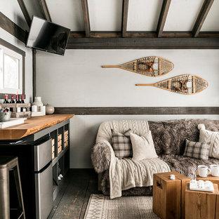 Immagine di un soggiorno stile rurale con angolo bar, pareti bianche, pavimento in legno verniciato, TV a parete e pavimento grigio