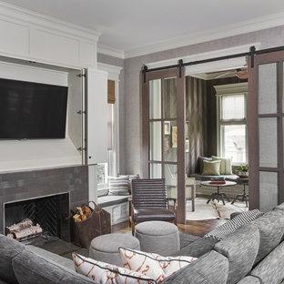 中サイズのコンテンポラリースタイルのおしゃれな独立型ファミリールーム (グレーの壁、濃色無垢フローリング、標準型暖炉、レンガの暖炉まわり、壁掛け型テレビ、茶色い床) の写真