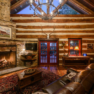 Example of a mountain style medium tone wood floor family room design in Austin with a corner fireplace and a wall-mounted tv