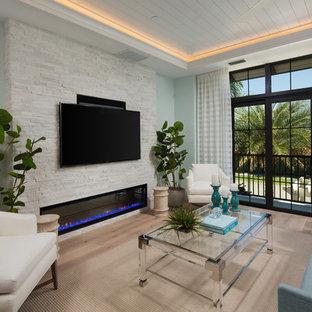 Modelo de sala de estar costera con paredes azules, suelo de madera clara, chimenea lineal, marco de chimenea de piedra, televisor colgado en la pared y suelo beige