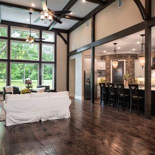 Foto di un grande soggiorno stile americano aperto con pareti nere, parquet scuro, camino classico, cornice del camino in pietra e TV a parete