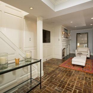 Modelo de sala de estar cerrada, tradicional renovada, pequeña, con paredes grises, suelo de ladrillo, chimenea tradicional, marco de chimenea de ladrillo y televisor colgado en la pared