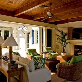 マイアミの中サイズのトロピカルスタイルのおしゃれなファミリールーム (白い壁、ライムストーンの床、標準型暖炉、木材の暖炉まわり、壁掛け型テレビ) の写真