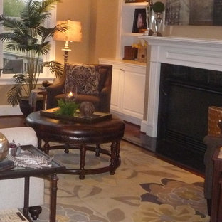 Mid-sized elegant enclosed light wood floor family room photo in Nashville with beige walls, a standard fireplace and a wood fireplace surround