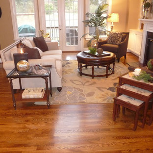 Mid-sized elegant enclosed light wood floor family room photo in Nashville with beige walls, a standard fireplace, a plaster fireplace and no tv