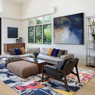 Exemple d'une salle de séjour tendance ouverte avec un mur blanc et un sol en bois clair.