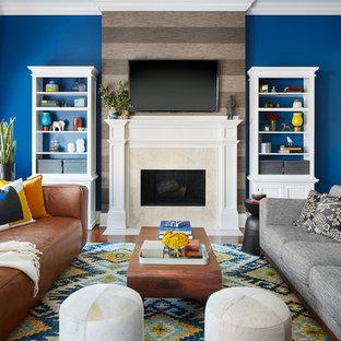 Aménagement d'une salle de séjour éclectique ouverte avec un mur bleu, un sol en bois brun, une cheminée standard, un manteau de cheminée en pierre, un téléviseur fixé au mur et un sol marron.