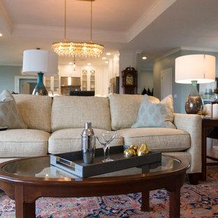 Cette photo montre une très grand salle de séjour chic avec un mur bleu, un sol en bois brun, une cheminée standard, un manteau de cheminée en carrelage, un téléviseur encastré et un sol marron.