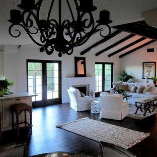 Foto di un soggiorno mediterraneo di medie dimensioni e stile loft con pareti bianche, parquet scuro, camino classico, cornice del camino in cemento e pavimento marrone