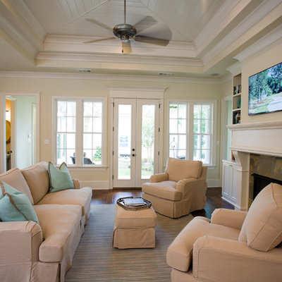 Elegant open concept dark wood floor family room photo in New Orleans with beige walls, a standard fireplace and a wall-mounted tv