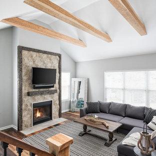 Réalisation d'une très grande salle de séjour style shabby chic ouverte avec un mur gris, un sol en bois brun, une cheminée standard, un manteau de cheminée en carrelage, un téléviseur fixé au mur et un sol multicolore.