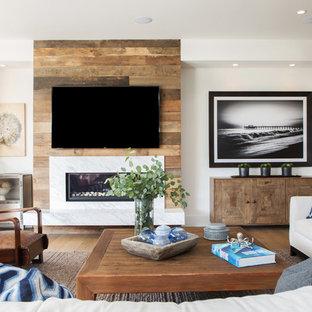 Idée de décoration pour une salle de séjour minimaliste avec un mur blanc, une cheminée ribbon, un téléviseur fixé au mur et un manteau de cheminée en pierre.