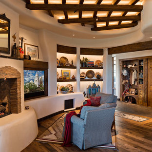 Family room - large southwestern open concept brown floor and medium tone wood floor family room idea in Phoenix with beige walls, a media wall, a standard fireplace and a stone fireplace