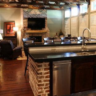 ヒューストンの大きいインダストリアルスタイルのおしゃれなファミリールーム (緑の壁、無垢フローリング、標準型暖炉、レンガの暖炉まわり、壁掛け型テレビ) の写真