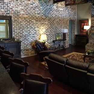 Réalisation d'une grande salle de séjour urbaine ouverte avec un mur vert, un sol en bois brun, une cheminée standard, un manteau de cheminée en brique et un téléviseur fixé au mur.