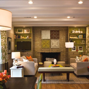 Example of a classic medium tone wood floor and brown floor family room design in San Francisco with green walls, a standard fireplace, a stone fireplace and a wall-mounted tv