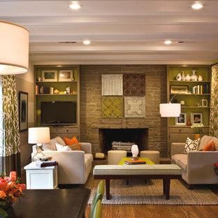 Imagen de sala de estar tradicional con paredes verdes, suelo de madera en tonos medios, chimenea tradicional, marco de chimenea de piedra, televisor colgado en la pared y suelo marrón