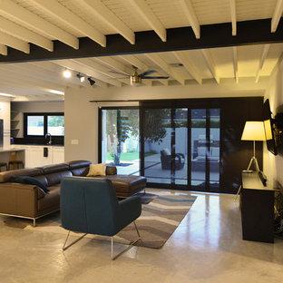 Exempel på ett mellanstort industriellt allrum med öppen planlösning, med vita väggar, betonggolv och en väggmonterad TV