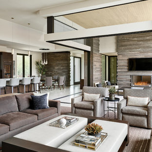 フェニックスの広いコンテンポラリースタイルのおしゃれなオープンリビング (茶色い壁、両方向型暖炉、石材の暖炉まわり、壁掛け型テレビ、白い床) の写真