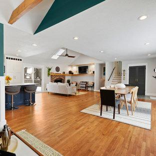 Inspiration pour une salle de séjour avec une bibliothèque ou un coin lecture traditionnelle de taille moyenne et ouverte avec un mur vert et un sol en bois brun.