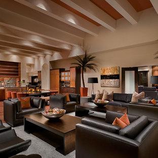 Ejemplo de sala de estar abierta, exótica, con paredes beige, suelo de madera en tonos medios y suelo marrón