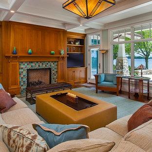 Cette photo montre une grande salle de séjour craftsman avec un sol en bois brun, une cheminée standard, un téléviseur encastré et un manteau de cheminée en carrelage.