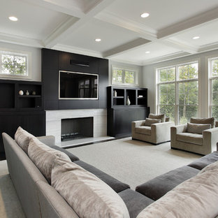 This is an example of a contemporary family and games room in Chicago with a standard fireplace, a stone fireplace surround and a built-in media unit.