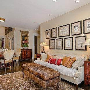 Diseño de sala de estar abierta, tradicional, pequeña, sin chimenea, con paredes beige, suelo de madera oscura y televisor retractable
