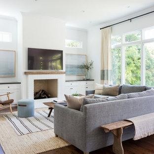 На фото: открытая гостиная комната в морском стиле с белыми стенами, темным паркетным полом, стандартным камином, фасадом камина из кирпича, телевизором на стене и коричневым полом