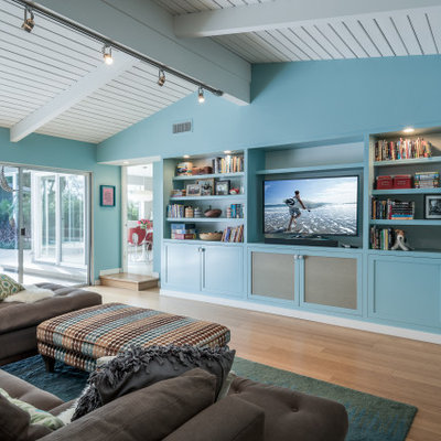Inspiration for a transitional open concept medium tone wood floor, brown floor, shiplap ceiling and vaulted ceiling family room remodel in Los Angeles with blue walls, no fireplace and a tv stand