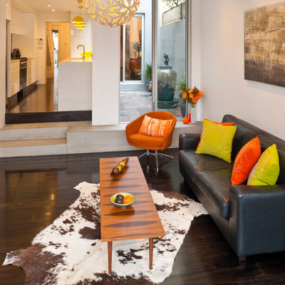 Inspiration for a contemporary dark wood floor and brown floor family room remodel in Sydney with white walls