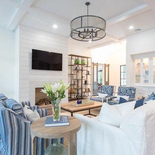 ヒューストンの大きいビーチスタイルのおしゃれなファミリールーム (白い壁、無垢フローリング、標準型暖炉、木材の暖炉まわり、壁掛け型テレビ、茶色い床) の写真